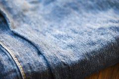 Textura das calças de brim da sarja de Nimes da roupa perto acima da dobra do teste padrão de calças de ganga no fundo de madeira fotografia de stock royalty free
