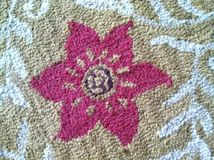 Textura de la alfombra con una flor rosada en el centro Imagen de archivo libre de regalías