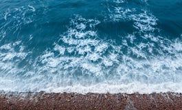 Textura de la creatividad del agua Nadada de las ondas a la orilla rocosa Visión superior Foto de archivo