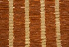 Textura de la estera de la paja de Brown con los modelos verticales Fotos de archivo libres de regalías