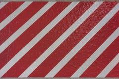 Textura de la etiqueta engomada con las rayas rojas y blancas diagonalmente en un concr imágenes de archivo libres de regalías