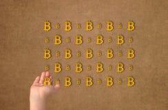 Textura de la moneda crypto de la muestra del bitcoin en la mano en fondo del oro Símbolo BTC Imágenes de archivo libres de regalías