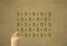 Textura de la moneda crypto de la muestra del bitcoin en la mano en fondo del oro Símbolo BTC Foto de archivo libre de regalías