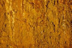 Textura de la pared de la arena de la arcilla del color amarillo con las porciones de grietas de diversa profundidad foto de archivo