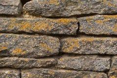 Textura de la pared de piedra de los ladrillos de piedra Ciérrese encima de fondo con el musgo amarillo Foto de archivo libre de regalías