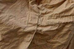Textura de la tela de Brown de un pedazo de ropa vieja arrugada fotos de archivo