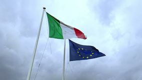 Textura de la tela que agita de la bandera de Italia y de la unión Europa en el cielo azul con las nubes, almacen de metraje de vídeo