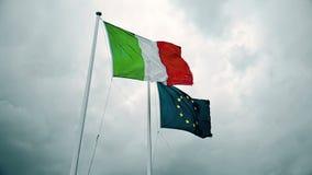 Textura de la tela que agita de la bandera de Italia y de la unión Europa en el cielo con las nubes, concepto de metrajes