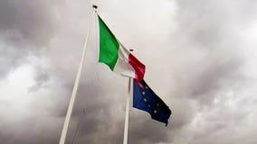 Textura de la tela que agita de la bandera de Italia y de la unión Europa en el cielo con el cielo nublado, concepto de metrajes