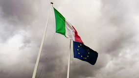 Textura de la tela que agita de la bandera de Italia y de la uni?n Europa en el cielo con las nubes, concepto de almacen de metraje de vídeo