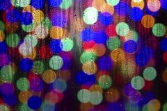 Textura de los descensos del agua sobre el vidrio Luces Defocused a través de una ventana mojada Imágenes de archivo libres de regalías