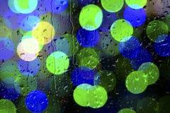 Textura de los descensos del agua sobre el vidrio Luces Defocused a través de una ventana mojada Fotos de archivo libres de regalías