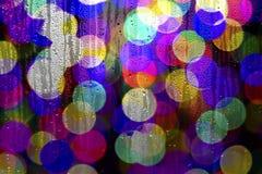 Textura de los descensos del agua sobre el vidrio Luces Defocused a través de una ventana mojada Foto de archivo libre de regalías