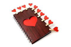 Textura de madeira do bloco de notas c com coração e os pregadores de roupa vermelhos em um fundo branco Imagens de Stock