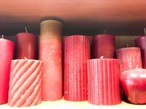 Textura de muchas diversas formas festivas de rojo, velas de la cera de Borgoña con las mechas que se colocan en fila Los anteced imagen de archivo libre de regalías