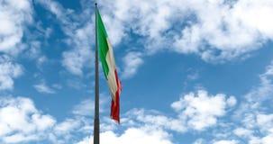 Textura de ondulação da tela da bandeira tricolor de Italia no céu azul com as nuvens brancas que movem-se no vento, ilustração royalty free