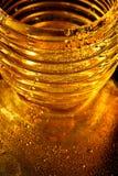 Textura de oro con descensos del agua Sed y su amortiguamiento Descensos de la miel sobre el vidrio Imagen de archivo libre de regalías