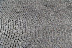 Textura de pedra cúbica da estrada em um papel de parede do fundo do dia ensolarado foto de stock