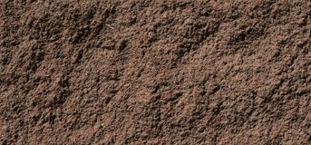a textura de pedra das paredes Brown-vermelhas iluminou-se pela luz solar brilhante foto de stock