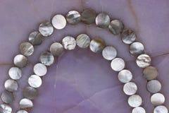 Textura de quartzo de Rosa com o ornamento pequeno da colar dos escudos da pérola da mãe fotografia de stock royalty free
