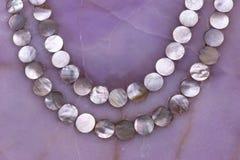Textura de quartzo de Rosa com o ornamento pequeno da colar dos escudos da pérola da mãe fotografia de stock