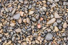 Textura de superfície de seixos molhados da praia do mar do tamanho médio e pequeno Fotografia de Stock