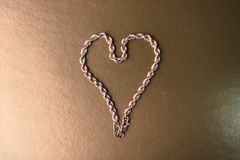 Textura de tejer único de la cadena festiva de oro hermosa en la forma de un corazón en un espacio del fondo y de la copia del or fotografía de archivo libre de regalías