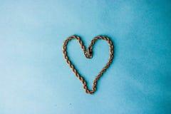 Textura de uma cara corrente festiva dourada bonita da tecelagem original na forma de um coração em um espaço azul do fundo e da  fotografia de stock royalty free