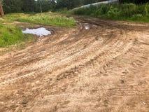 Textura de uma estrada de terra má suja da estrada de terra com poças e de lama de secagem da argila com quebras e rotinas Fora d fotografia de stock royalty free