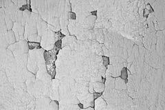 Textura de uma parede rachada cinzenta A pintura velha pode ser vista através das quebras na parede imagens de stock