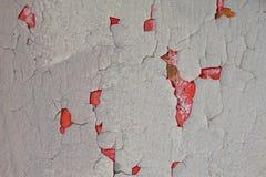Textura de una pared agrietada gris La pintura roja vieja se puede ver en la pared imagen de archivo libre de regalías