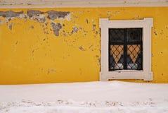 Textura de una pared amarilla con una ventana rodeada por la nieve imagen de archivo libre de regalías
