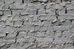 Textura de una pared de ladrillo con las combas del cemento entre los bloques cubiertos con la pintura gris fotografía de archivo