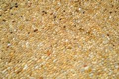 Textura de una pared de piedra, de caminos de pequeño alrededor y de piedras ovales con la arena con las costuras del viejo marró foto de archivo