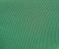 Textura de una tela tejida verde de la prenda impermeable del sintético Foto de archivo