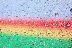 Textura del agua del arco iris sobre un vidrio Imagenes de archivo