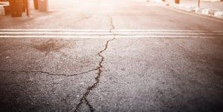 Textura del camino viejo con las grietas Superficie del asfalto en la calle Resplandor de la luz Tamaño de la bandera del web 16  Foto de archivo