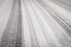 Textura del fondo de la carretera de asfalto cubierta con las pistas de la nieve y del neumático Foto de archivo libre de regalías
