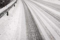 Textura del fondo de las barreras de desplome y de la carretera de asfalto cubiertas con las pistas de la nieve y del neumático, Foto de archivo