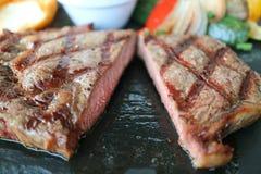 Textura do close up do bife grelhado médio cortado do ribeye servido na placa de pedra quente imagem de stock