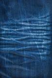 Textura do fundo da calças de ganga com plissados Fotografia de Stock Royalty Free
