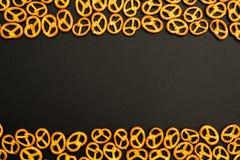 Textura do fundo de mini pretzeis saborosos salgados no formulário tradicional do conjunto de dobradiça em um fundo preto Espaço  imagem de stock