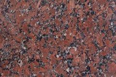 Textura do granito Base castanho-avermelhado com os pontos pretos e cinzentos usado como um fundo foto de stock