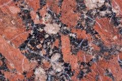 Textura do granito Base castanho-avermelhado com os pontos pretos e cinzentos usado como um fundo imagem de stock
