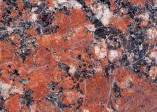 Textura do granito Base castanho-avermelhado com os pontos pretos e cinzentos usado como um fundo imagens de stock