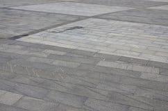 A textura do granito que pavimenta telhas de uma variedade de plataformas dadas forma quadradas sob o sunligh brilhante Fotografia de Stock Royalty Free