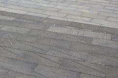 A textura do granito que pavimenta telhas de uma variedade de plataformas dadas forma quadradas sob o sunligh brilhante Imagens de Stock