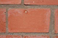 A textura do tijolo vermelho e do cimento como parte de uma parede molda o close-up Imagens de Stock