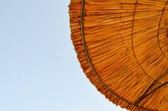 Textura dos guarda-sóis naturais da palha bonita feitos do feno em um recurso tropical do deserto, descansando contra foto de stock