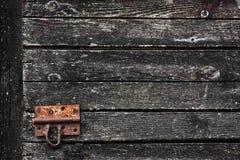 Textura escura de madeira velha do grunge para o fundo com a trava de porta oxidada Imagem de Stock